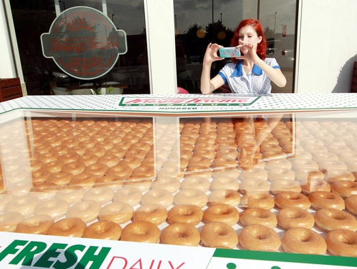 A woman snaps a photograph of Krispy Kreme's giant box of 2,400 doughnuts on Sept. 22 in North London, England. The Double Hundred Dozen box of doughnuts was prepared by eight staff members at the Enfield Hotlight store.