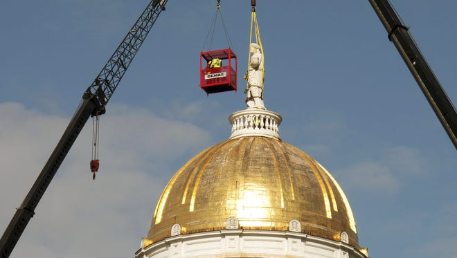 The 80-year-old statue of Ceres, the goddess of agriculture, is taken down from the top of the Vermont Statehouse in Montpelier, Vt., on Monday April 2, 2018. The wooden statue was believed to be rotting and it is headed to a warehouse where it can dry out. (AP Photo/Wilson Ring)