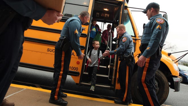 Kindergartener Devin Morin comes off his bus to high fives and gifts as Roxbury Police 'pull over' a bus of students at Jefferson Elementary School, a surprise thank you for donating to their food drive. The police gave the students badges and gift certificates. November 12, 2015, Succasunna, NJ.