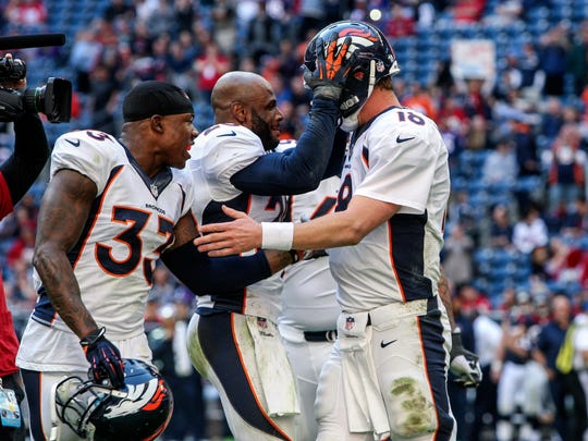 Dec 22, 2013; Houston, TX, USA; Denver Broncos quarterback Peyton Manning (18) is congratulated by teammates after throwing a touchdown during the fourth quarter against the Houston Texans at Reliant Stadium. The touchdown pass set an NFL record for touchdown passes in  a season.