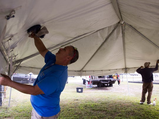 Gilbert Rodriguez, left, owner of Magic City Productions, and Yasmani Diaz clean the underside of a tent as they set up one of their clients for the 46th Annual Everglades Seafood Festival on Wednesday, Feb. 7, 2018, in Everglades City, Fla.