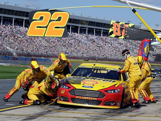 Crew members perform a pit stop on Joey Logano's car the NASCAR Sprint Cup series auto race at Charlotte Motor Speedway in Concord, N.C., Sunday, Oct. 11, 2015. (AP Photo/Terry Renna)