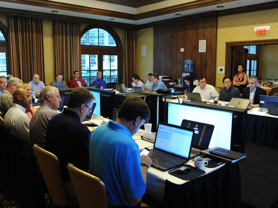 Reporters take part in a mock College Football Playoff selection committee exercise Thursday in Grapevine, Texas.
