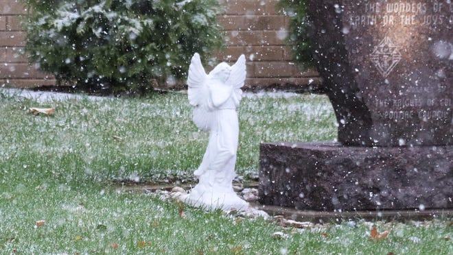 A statue of angel stands in front of St. Mary's Church as snow falls Monday morning. This was the first snow of the season but it was gone by afternoon.