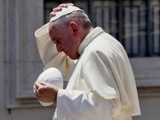 Pope Francis exchanges his skull cap with one donated to him as he leaves at the end of his weekly general audience in St. Peter's Square at the Vatican on Wednesday.