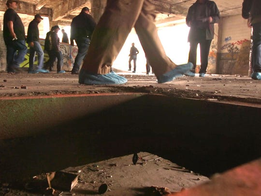 Participants of a tour of the Packard Plant walk around a hole in the floor of the plant.