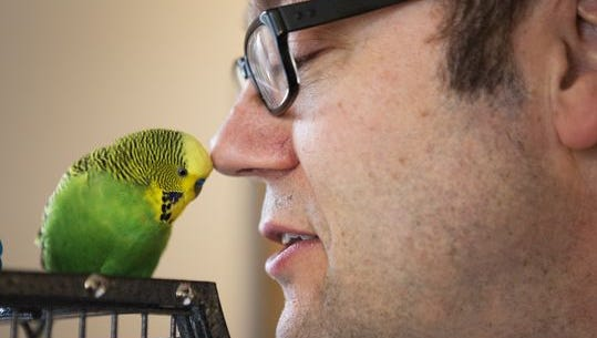 File Photo of Kevin Bolton, of Penfield, speaking with Disco the parakeet.