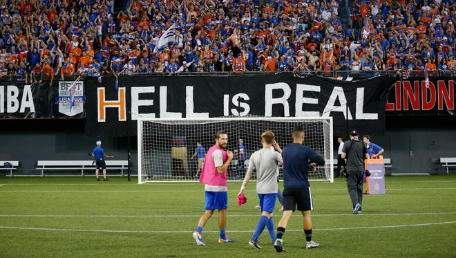 """Fans drop a """"Hell is Real"""" banner, referring to a series of billboards on I-71 between Cincinnati and Columbus after the US Open Cup soccer match between FC Cincinnati and Columbus Crew at at Nippert Stadium on June 14, 2017."""