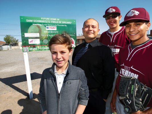"Sam Schwartz, 13, foreground, is raising funds for a ""Field of Dreams"" for Lydia Patterson Institute at 517 S. Florence in South El Paso. The century-old school has never had its own playing field. With him is school principal Ernie Morales and baseball players Eduardo Mota and Luis Santillan, right. The land behind them where the field will be built was puchased by the Hunt Family Foundation."