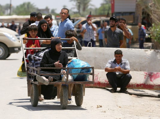 """Hadi Mizban — The Associated Press In this Saturday, May 16, 2015 photo, Iraqis fleeing from their hometown of Ramadi walk on a street near the Bzebiz bridge, 65 kilometers (40 miles) west of Baghdad. Muhannad Haimour, a spokesman for the governor of Iraq's Anbar province, said Sunday, """"Ramadi has fallen,"""" to the Islamic State group. He also said the military's operational command in the city has been taken as well."""
