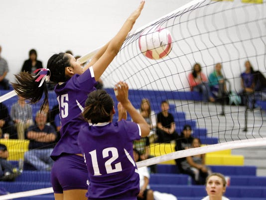 Kirtland's Alexandria Cambridge (12) helps block a spike during a game against Bloomfield on Oct. 30, 2014, at Bobcat Gym in Bloomfield.