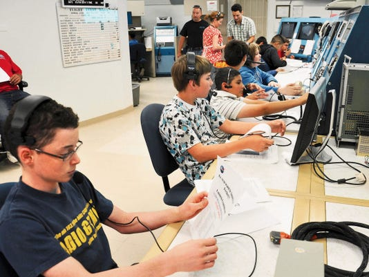 Courtesy photo — U.S. Army by Laura Almaraz Students read the instructions before a simulated NASA launch as they become familiar with their stations in the control room.