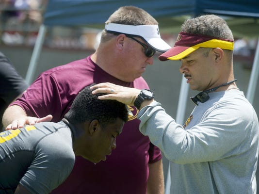 Eric Lauer, an offensive coordinator with Mountain Pointe High School football team, checks on an injured player during an early June seven-on-seven tournament on the Arizona State University campus. Lauer, biracial and adopted, said football helped him fit in growing up in York.