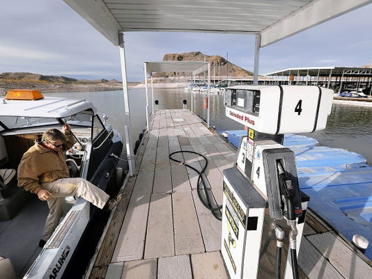 Neal Brown, owner of the three marinas at Elephant Butte reservoir, climbs out of his boat after touring the lake.