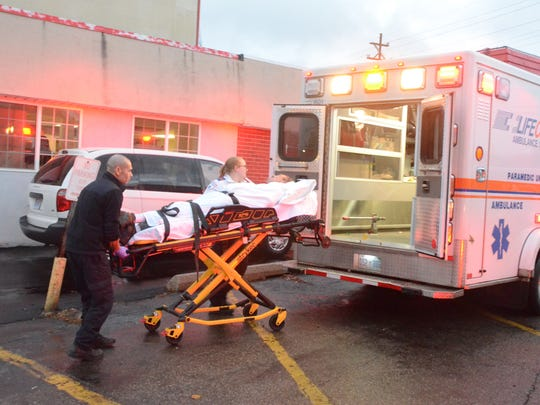 Paramedics from Lifecare Ambulance move a patient from