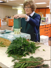 Rhonda Wolff, shapes green foam to begin creating a floral arrangement on Friday, Dec. 15, 2017, at Plasterer's Florist. She has been with Plasterer's for 50 years.