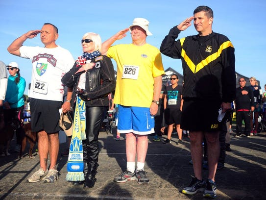 Runners salute before participating in a past Honor