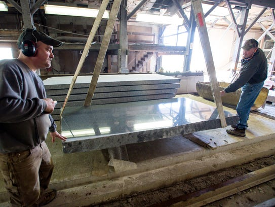 Workers lower a slab of polished granite at Buttura