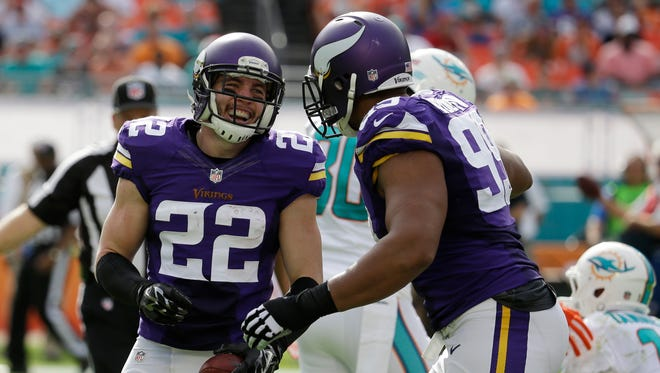 Minnesota Vikings free safety Harrison Smith (22) is congratulated by  tackle Corey Wootton after Smith intercepted a pass by Miami Dolphins quarterback Ryan Tannehill on  Sunday.