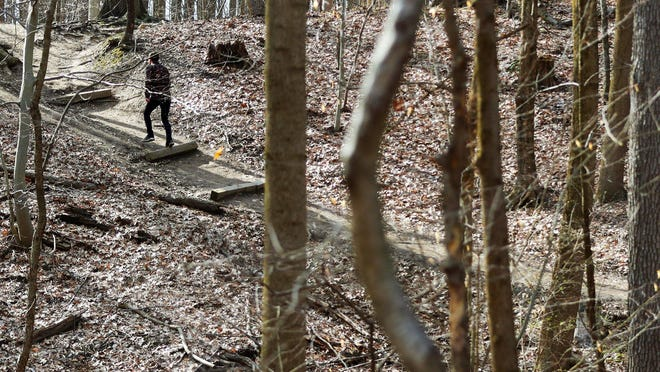 A hiker ascends a trail at Sand Run Metro Park in Akron.