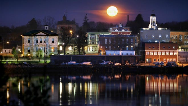 The nearly full moon sets at dawn over Bath, Maine, in this April 2006 photo.