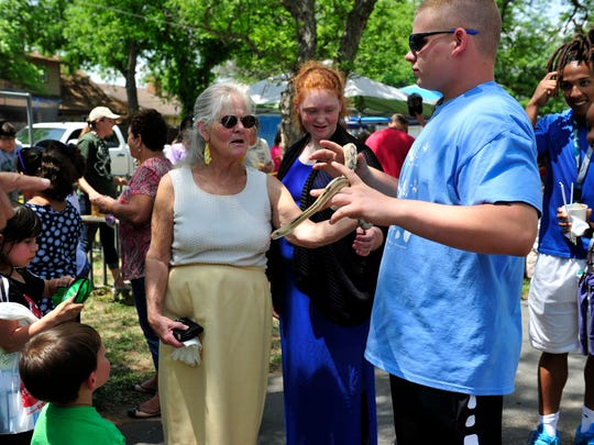 A crowd gathers around Hunter Stelly and Capone, a Trans Pecos rat snake from the San Angelo Nature Center during the 2015 Children's Fair.