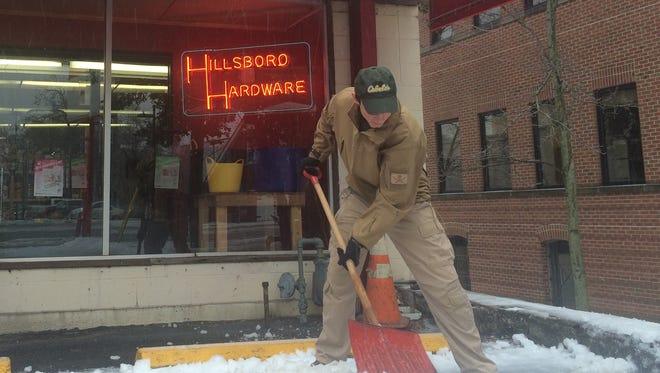 Hillsboro Hardware employee J.P. Hartmann shovels snow outside the business on 21st Avenue after Monday's winter storm.