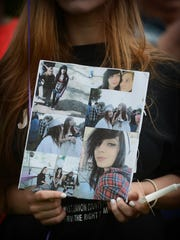 Julie Farver holds a collage of pictures of  Victoria