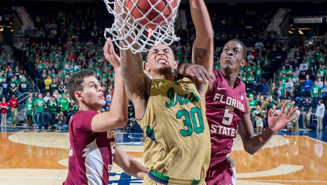 Notre Dame Fighting Irish forward Zach Auguste (30) dunks as Florida State Seminoles center Boris Bojanovsky (15) and forward Jarquez Smith (5) defend in the second half at the Purcell Pavilion. Notre Dame won 83-63.