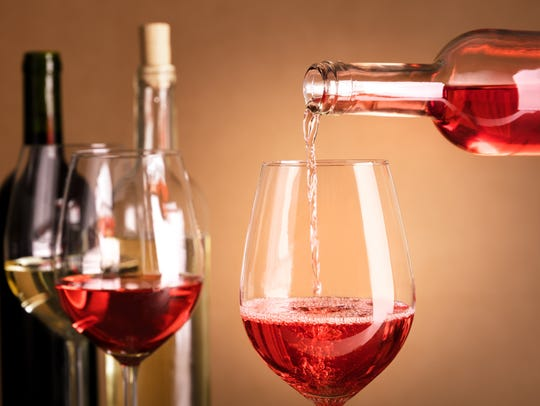 Rose wine being poured into a glass from a bottle,