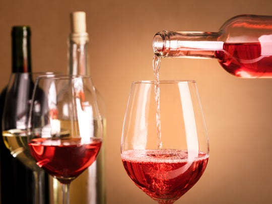 Rose wine being poured into a glass from a bottle, on a dark background, with copy space and other glasses and more bottles in the blurred background. Design template for a tasting invitation
