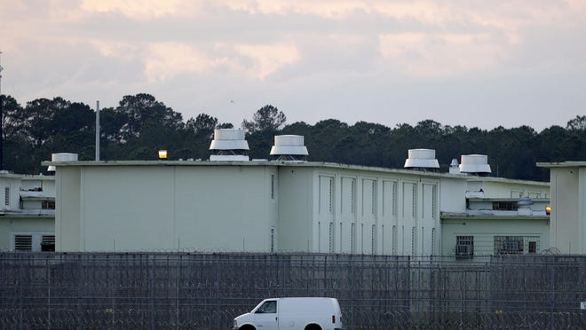 A van drives past a barbed wire fence outside Florida State Prison near Raiford.