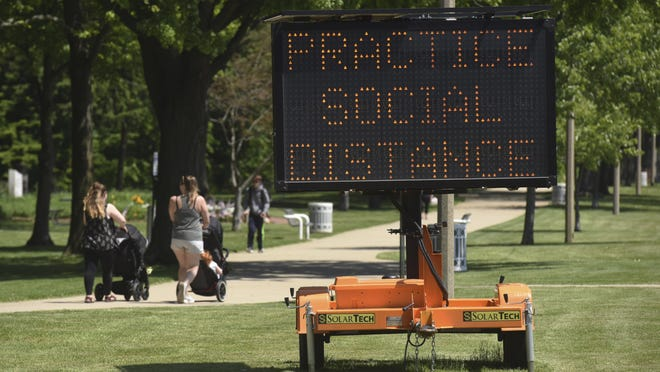 A sign along the bluff in downtown St. Joseph, Mich., encourages social distancing Tuesday, June 2, 2020, as the state slowly continues to open after being shut down for months due to the COVID-19 pandemic.