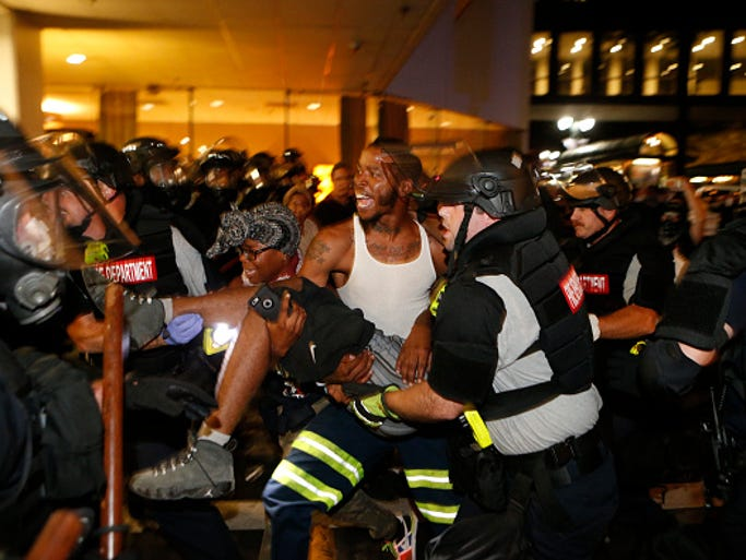 Police and protesters carry a seriously wounded protester