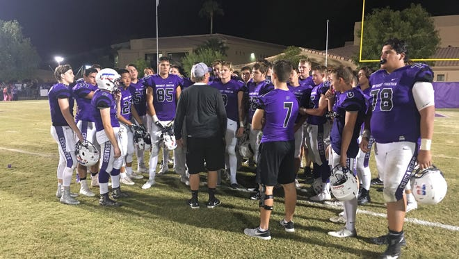 Northwest Christian coach David Inness meets with his team after its 38-13 win over Odyssey Institute on Friday, Sept. 29, 2017.
