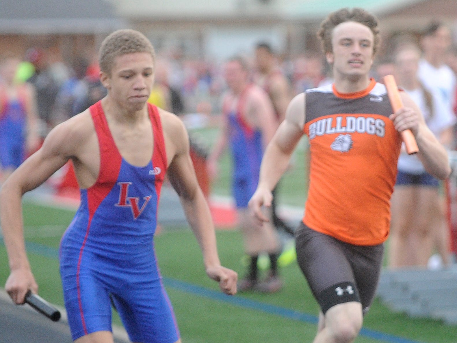 Licking Valley's Maaliq Elliott and Heath's Nick Lines cross the finish line Thursday at the end of sprint medley during the Dick Houston Relays.