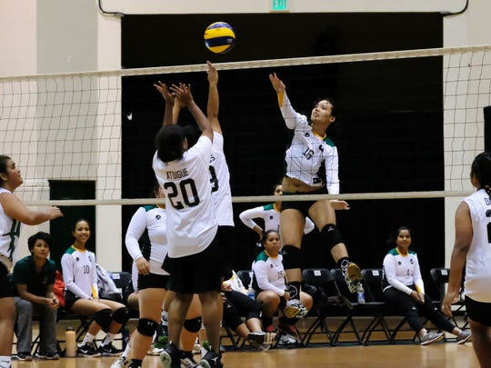 UOG's Jasmine Almoguera spikes over the late block of PIU in their Guam Women's College Volleyball League game Thursday night, Feb. 2, 2017, at the UOG Calvo Field House. UOG won 3-1.