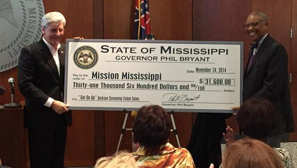Gov. Phil Bryant presents a check to Mission Mississippi