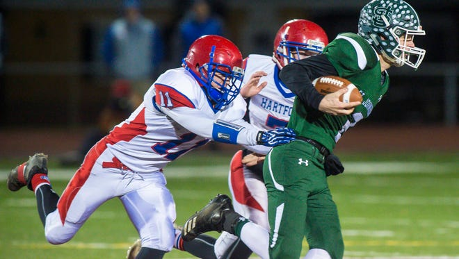 St. Johnsbury's Jacob Cady, right, is pursued by Hartford's Nick Porter in the Division 1 high school football state championship in Rutland on Saturday, November 11, 2017.