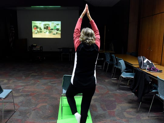 "Bonnie Seibert of Warrick County stretches while taking a yoga class for middle-aged adults at the McCollough branch of the Evansville Vanderburgh Public Library in Evansville Tuesday.  The free weekly exercise program called ""Simply Fit"" rotates between yoga and cardio workouts at the library."