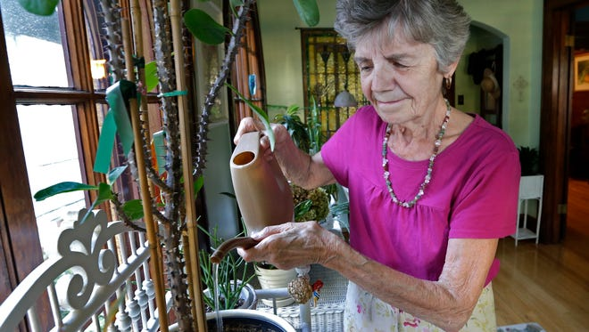 Judy Howden tends to her plants in her home. She had fallen a few times, once seriously in 2013, before she got introduced to a fall-prevention workshop called Stepping On.