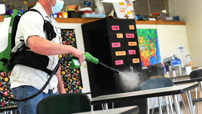 John Phelps, head custodian at Glenwood Intermediate School in Plain Township, begins the nightly task of spraying surfaces with an electrostatic sprayer to help reduce the potential spread of the COVID-19 virus. Plain Local Schools has spent an additional $475,225 on cleaning supplies, equipment and technology due to the pandemic.