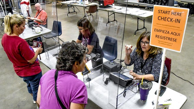Election workers Beth Moser, right, and Gina Parr sign in local residents to be able to cast their ballots in August during the primary election at a voting site in the Finney County Fairgrounds 4-H building.