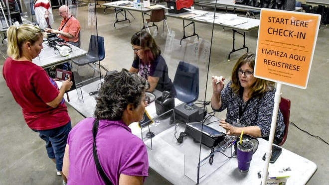Election workers Beth Moser, right, and Gina Parr sign in local residents to be able to cast their ballots from behind plexiglass Tuesday during the primary election at a voting site in the Finney County Fairgrounds 4-H building.