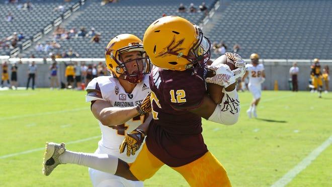 ASU wide receiver John Humphrey (12) catches a touchdown behind linebacker Matthew Thompson (47) during Saturday's ASU football spring game at Sun Devil Stadium in Tempe.