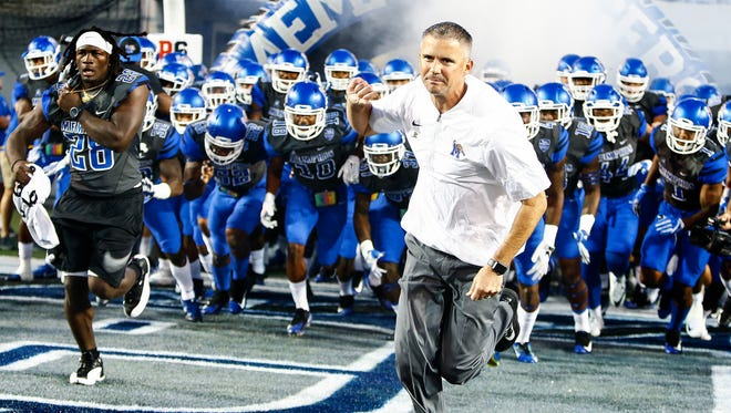 University of Memphis head coach Mike Norvell (right) lead his team onto the field as take one Southern Illinois University at the Liberty Bowl Memorial Stadium Saturday, September 23, 2017.
