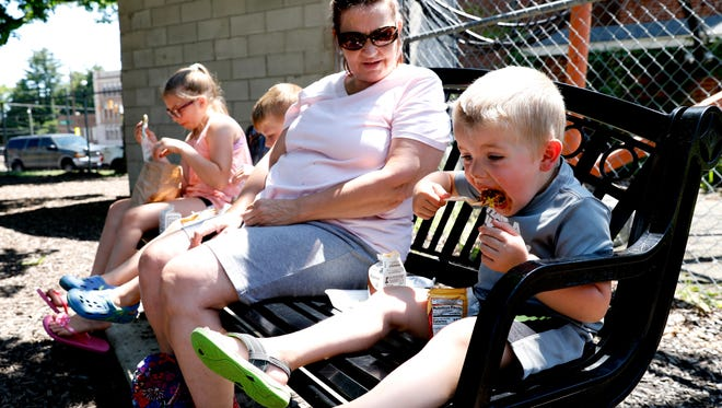 Miles Carroll, 3, takes a bite of a walking taco as he has lunch with his siblings Abby Carroll, 10, left, Jackson Carroll, 5, and grandmother Chris Tufts Friday, June 15, 2018, at Firehouse Park in Lancaster. This was the first time this year Tufts had brought the children to the daily free summer lunch program, but she said they came many times last summer on days she was caring for them. The Afterschool Program's of Lancaster's Lunch Club program runs through August 10. It's held Monday through Friday at locations throughout the city at two different times.