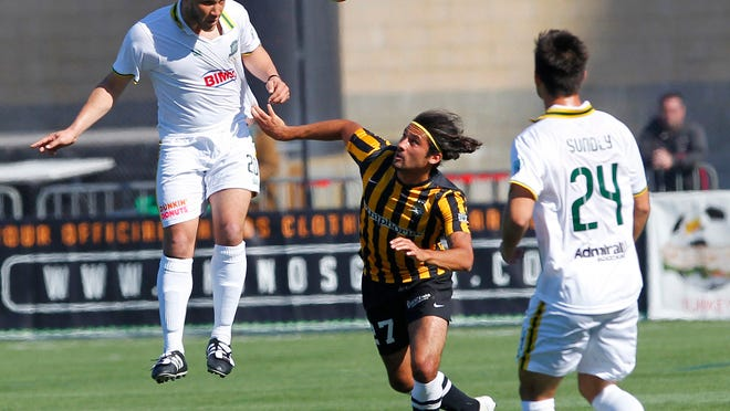 Rochester's Tony Walls, left, heads a ball to teammate Alec Sundly (24) over Charleston's Adam Mena during their home opener of USL soccer action between the Charleston Battery and the Rochester Rhinos at Sahlen's Stadium in Rochester Sunday evening, April 27, 2014.
