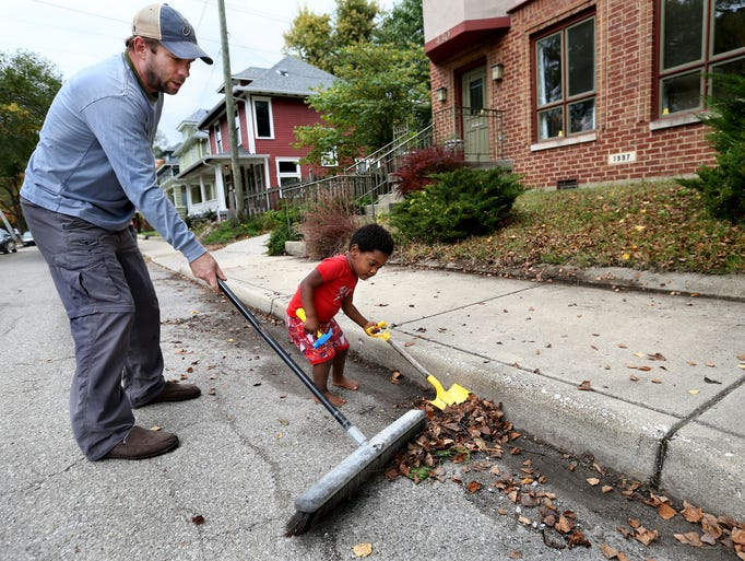 Ruben Reynolds, 2, helps his father Nate Reynolds clean