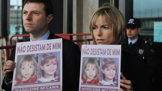 """Gerry and Kate McCann pose with boards portraying their missing daughter Madeleine reading """"Don't give me up"""" as they leave the Tribunal Civil de Lisboa in Lisbon on Feb. 10, 2010."""